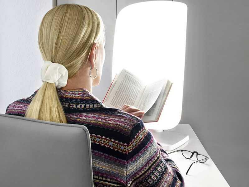 eine Frau liest ein Buch während der Lichttherapie
